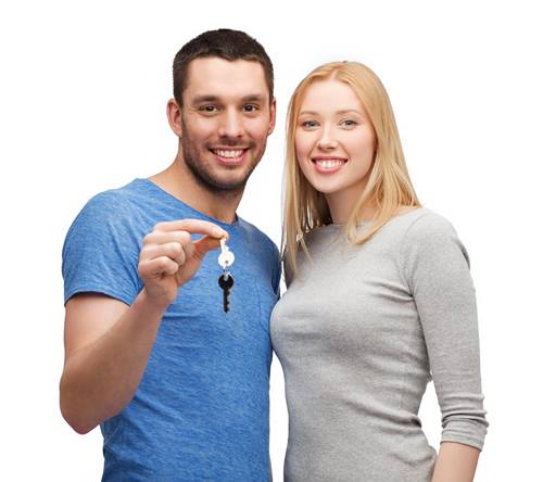 young couple smiling with a key to house