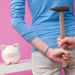 Young woman with hammer behind back thinking about smashing her piggy bank