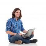 Young male IT professional sitting on the ground with a laptop, smiling