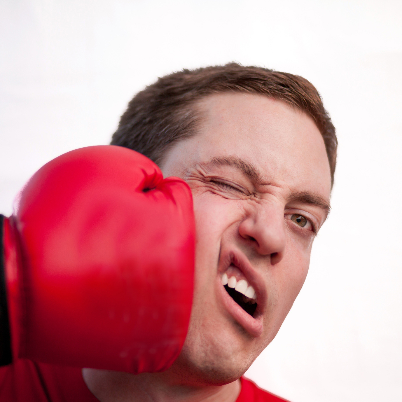 Man being hit in the face with a red boxing glove
