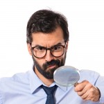 Man with a magnifying glass, glasses and beard wearing a blue shirt