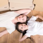 Young couple in white shirts lying on the ground with moving boxes