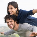 Young woman smiling and piggy backing her boyfriend