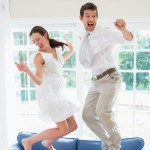 Young couple jumping up and down on a blue couch in ecstasy