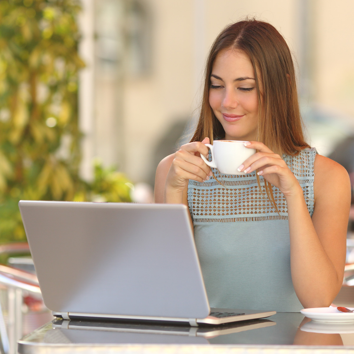 Young, self-employed woman sipping coffee and working on a laptop