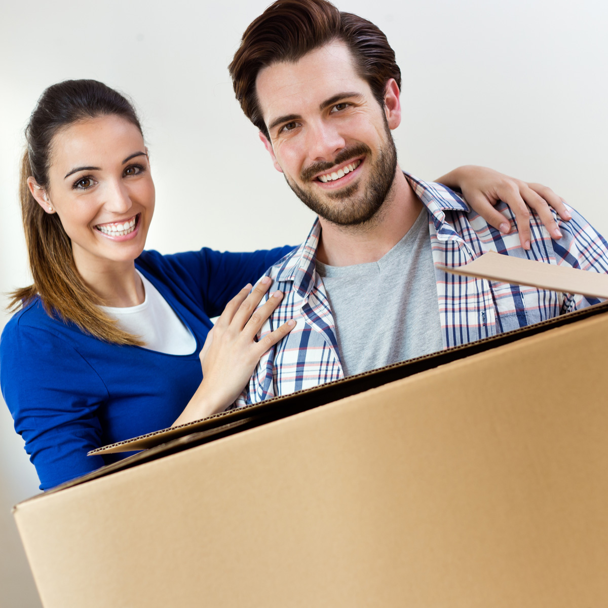 Young, smiling couple with a moving box