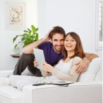 Young couple sitting on the couch planning to buy a home