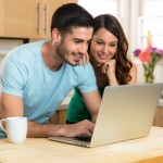 Smiling couple learning about mortgage repayments on the internet