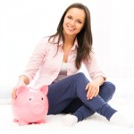 Young woman sitting and smiling beside her full piggy bank