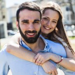 Young couple smiling and standing together in the sun