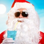 Santa in sunglasses on a beach and drinking a blue cocktail
