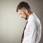 Businessman in white shirt and red tie, sad because of job loss