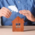 man holding umbrella over a wooden house model depicting protection by lenders mortgage insurance against default